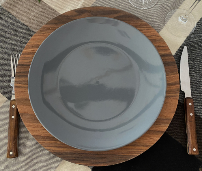A place setting with wooden handled fork and knife, a faux wood charger, a gray dinner plate on a plaid throw