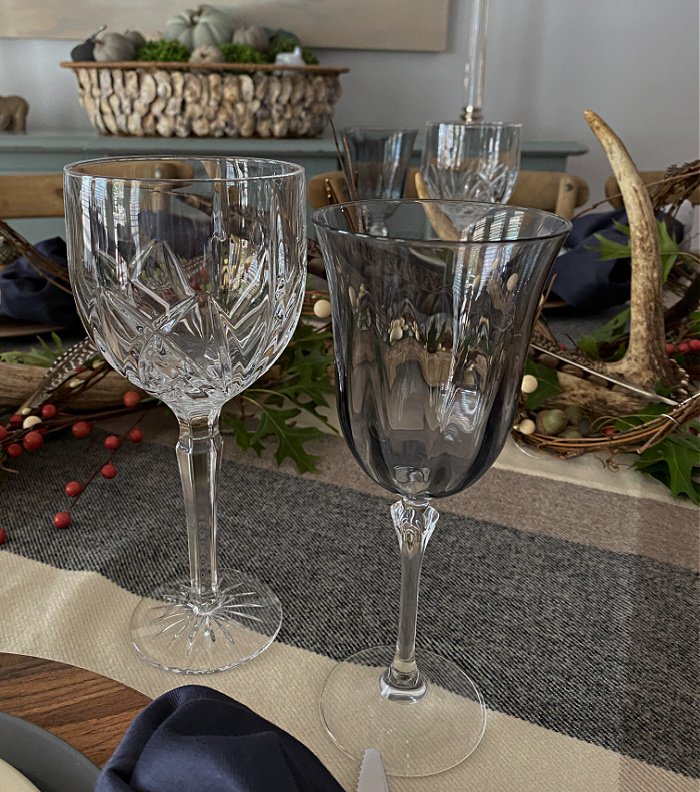 IN the background, a basket with greenery and gray pumpkins on a blue sideboard.  In the foreground a tablescape showing clear crystal water goblets and gray wine goblets.