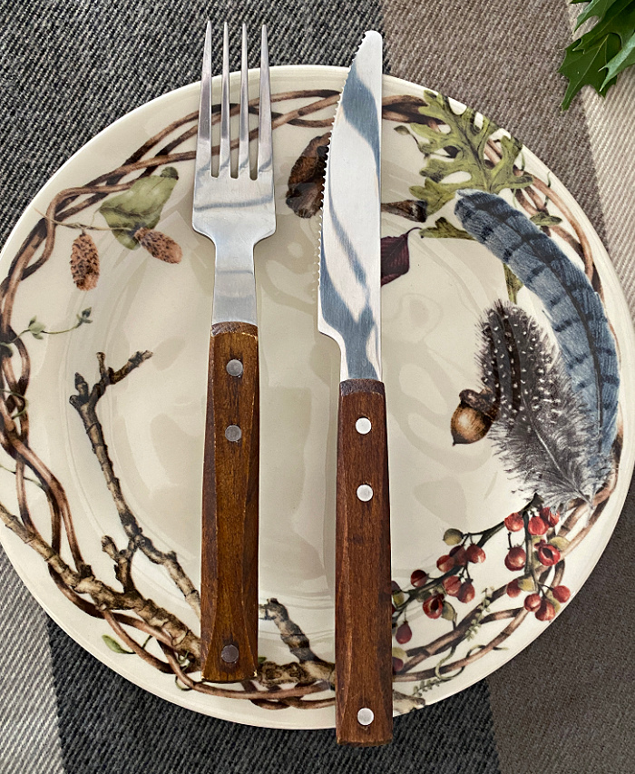 A salad plate that is cream color with branches around the edges also decorated with berries, acorns, feathers and fungi with a wooden handled knife and fork laid across the plate