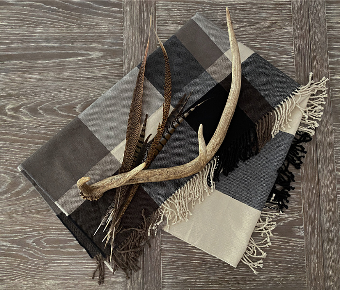 A folded plaid throw of cream, black, gray and brown on a wooden table.  A large antler shed and some pheasant feathers.