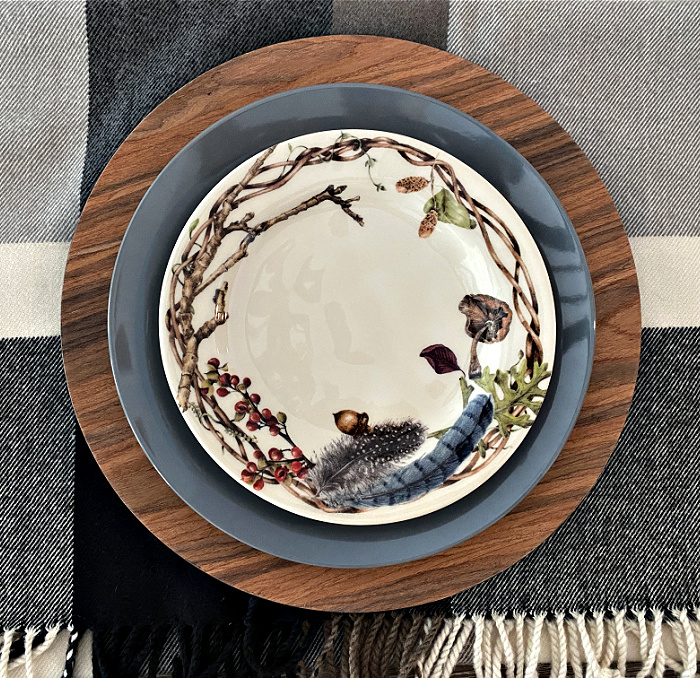 A place setting a faux wood charger, a gray dinner plate topped with a salad plate that is cream color with branches around the edges also decorated with berries, acorns, feathers and fungi set on a plaid throw