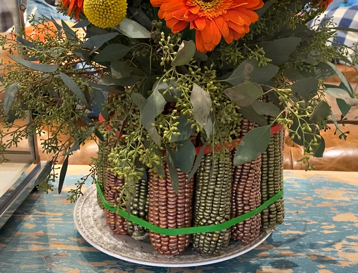 Flowers arranged in a glass vase that is surrounded by painted ears of corn and wrapped with rubber bands and sitting on a decorative white plate