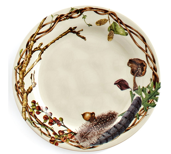 A salad plate that is cream color with branches around the edges also decorated with berries, acorns, feathers and fungi